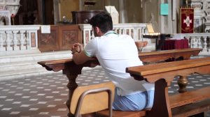 videoblocks-young-man-sitting-and-kneeling-in-church-praying_rcg0ehvpq_thumbnail-full01